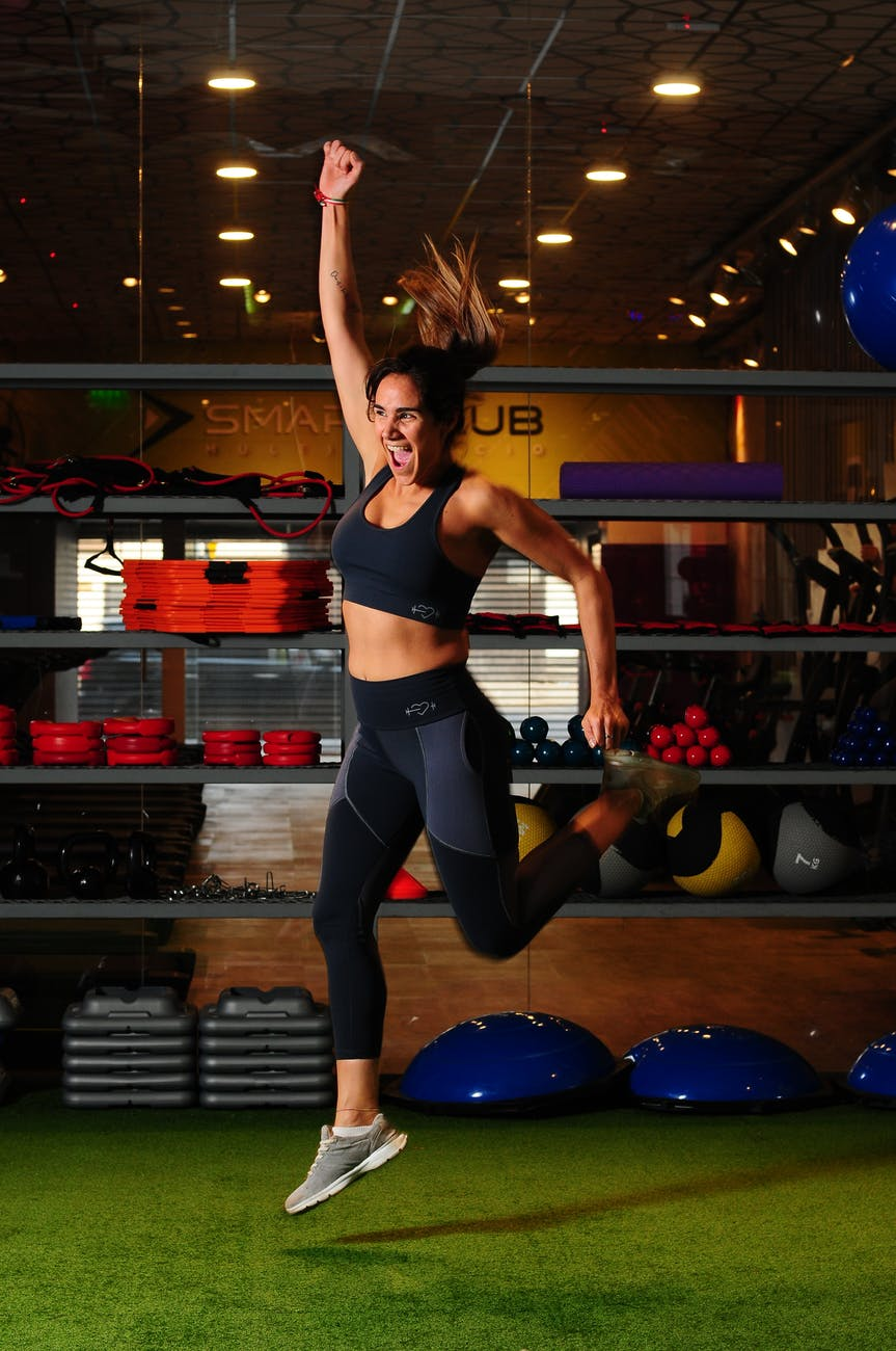 woman jumping while raising one hand