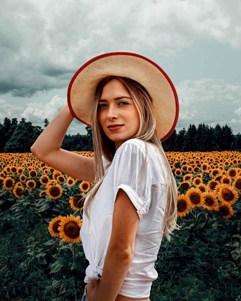 photo of woman in white short sleeved crop top and brown sun hat posing by sunflower field