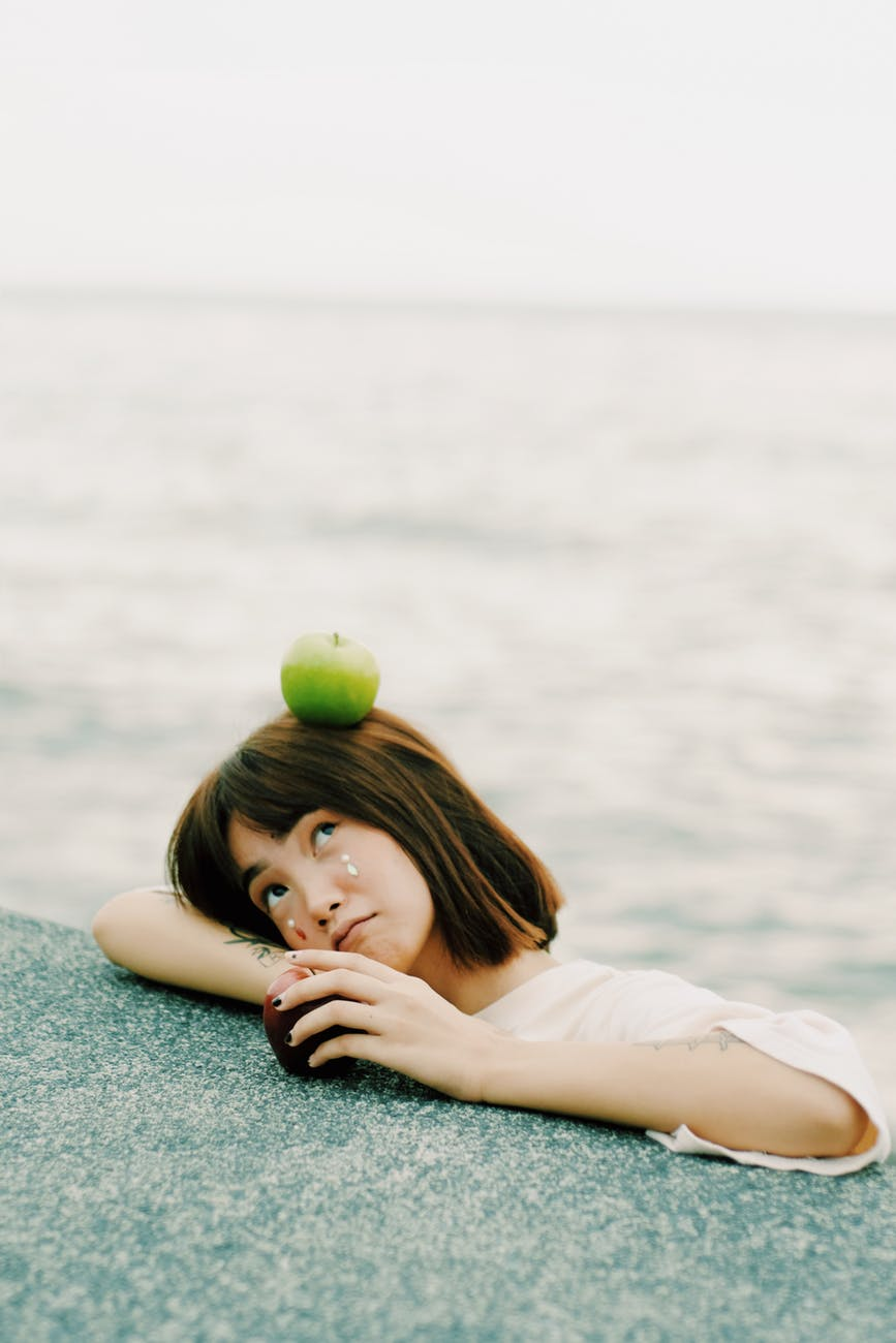 green apple on girl s head