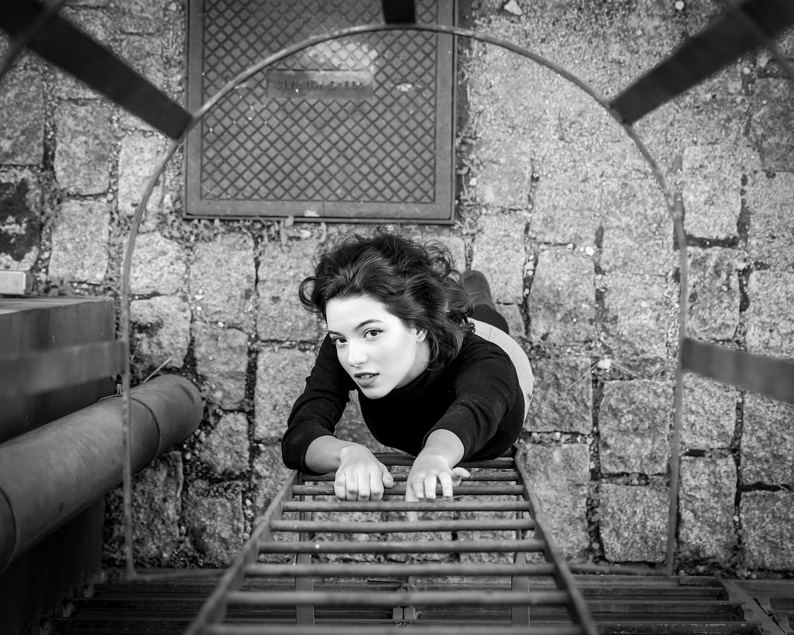 gray scale photo of a woman about to climb the fire escape ladder